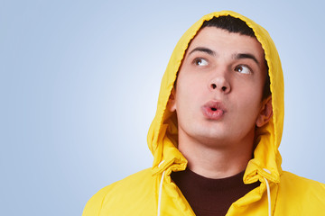 Horizontal portrait of astonished brunet man looks with surprisment up, wears trendy anorak with hood on head, poses against blue background with copy space for your advertisment or promotional text