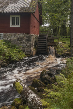 An old water mill located at a river with red waters coloured by iron compounds