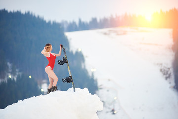 Attractive female snowboarder wearing red swimsuit, posing with snowboard on snowy hill at ski resort. Ski season and winter sports concept