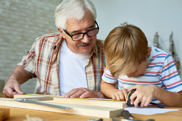Portrait of old man teaching cute little boy woodwork, making wooden models together working at desk in small studio