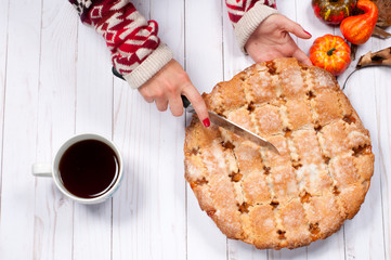 Woman cutting of pie. Black tea and apple pie
