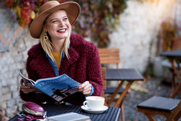 Portrait of excited young woman reading journal about traveling with enjoyment. She is laughing while having rest in cozy cafeteria. Copy space