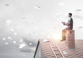 Man on brick roof reading book and paper planes flying in air