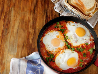 Foto op Canvas Gebakken Eieren A pan of fried eggs with tomato sauce and parsley on a wooden background. Shakshuka a traditional meal of the Jewish cuisine