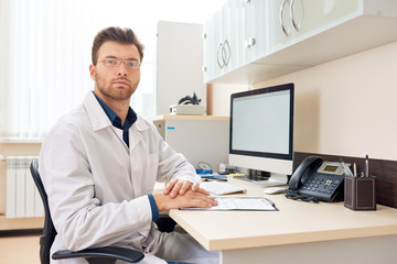 Portrait of mature medical professional sitting at desk in office posing confidently and looking at camera, copy space