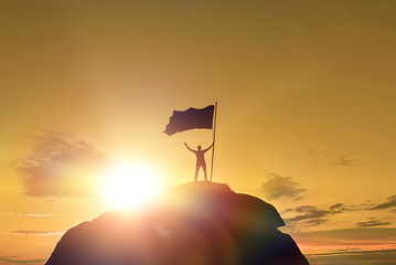 High achievement, silhouettes of men, victory flag on top of the mountain, hands up. A man on top of a mountain. Conceptual design. Against the dramatic sky with clouds at sunset.