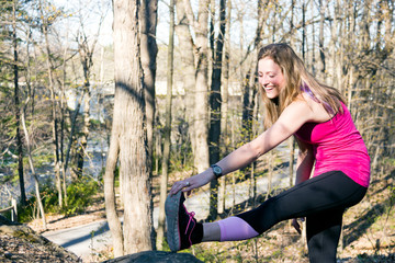 Fit girl stretches leg before running in the woods