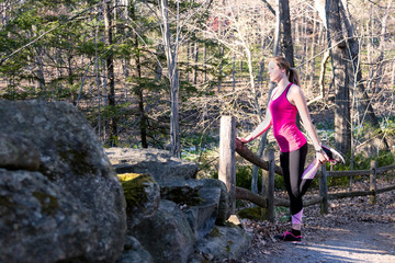 Fitness woman in the forest stretching legs before jogging