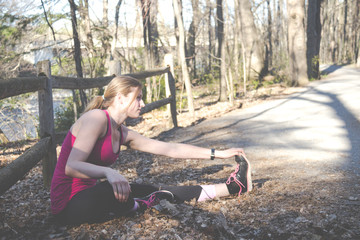 Fitness woman doing stretching during outdoor training workout.