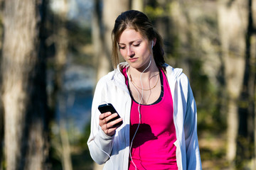 Young woman selects music on smartphone prior to running in nature