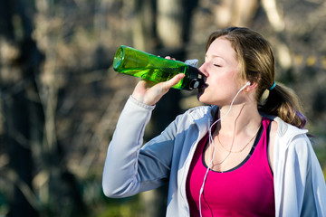 Female runner takes a break from jogging and drinks water