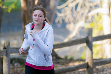 Female fitness girl jogging on path in nature landscape outside.