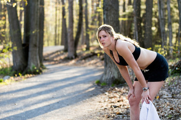 Sporty girl in nature stops to take a rest from jogging catching breath. Fitness lifestyle concept.