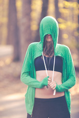 Woman fitness model with sports bra and sweatshirt hoodie on nature trail.