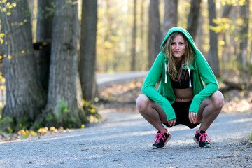 Female fitness model in sports bra with hoodie on nature trail. Fitness lifestyle concept.