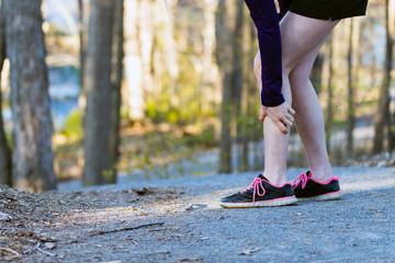 Sports injury leg cramp on running trail.