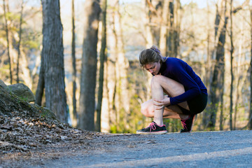 Shin splint running injury for young woman jogging on nature trail
