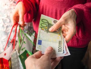 Customer pays euro bills cash while shopping.