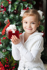 Happy girl in white jacket with gift near christmas tree