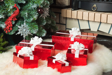 Red gift boxes near christmas tree and fireplace