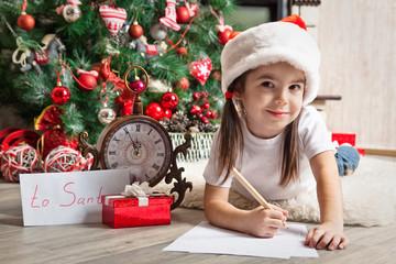 Thoughtful girl in Santa hat writes letter to Santa