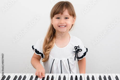 Cute little girl plays on piano, synthesizer  Training  Education