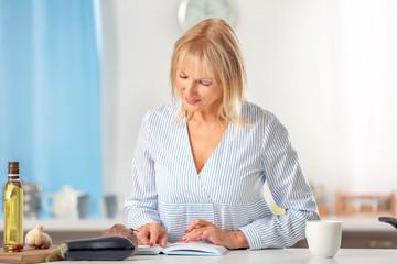 Beautiful mature woman reading recipe book in kitchen