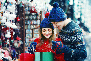 Outdoor waist up portrait of young beautiful happy smiling couple holding and looking at bags. Shopping at the street Christmas fair. Models wearing stylish winter clothes. Snowfall. Copy, empty space