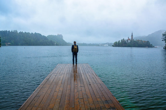 traveler man standing on the lake wooden pier in fog against island with church. travel lifestyle concept