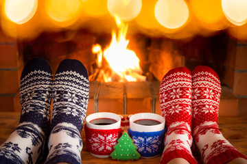 Couple in Christmas socks near fireplace