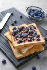 Board with tasty toasts, jam and blueberries on table