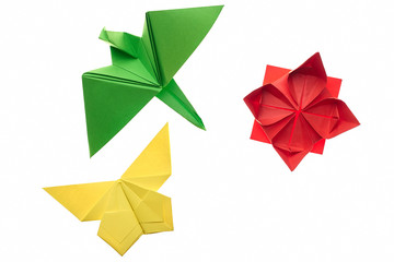 Crane, butterfly and lotus origami on white. Red, green and yellow paper. Hand crafting project idea for kids.