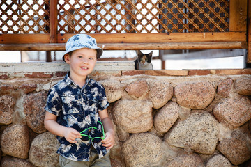 Little tourist boy is photographed with a cat