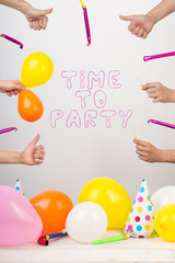 equipment, party, fiest concept. in the center there is words created of funny font with pink line, they say that it is time for party, and lots of balloons and whistles are lying around
