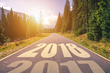 Empty asphalt road and New year 2018 concept. Driving on an empty road in the mountains to upcoming 2018 and leaving behind old 2017. Concept for success and passing time.
