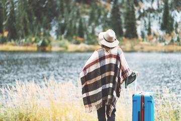 Woman tourist wearing poncho and hat with bright blue suitcase looking at stunning mountain wilderness. Wanderlust and boho style