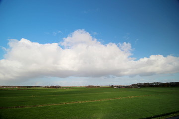 Big white cloud in blue sky over the Zuidplaspolder in Moordrecht, The Netherlands in wide angle view
