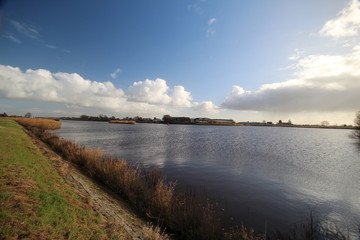 Wide angle overview of blue sky, white clouds and river Hollandse IJssel in Moordrecht, Netherlands