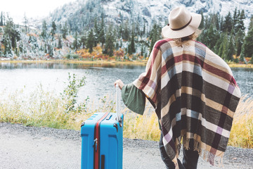Woman wearing poncho and hat with bright blue suitcase looking at stunning mountain lake wilderness. Wanderlust and boho style