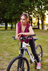 Cute girl riding a bike in the park on a nature background