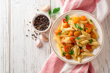 Penne pasta with pumpkin, chilli and parsley in plate on white wooden background