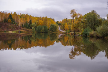 The autumn forest and the road on the hills are reflected in the calm water of the forest lake.