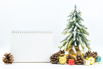 Christmas or New Year background with blank note pad,pine cones,gift box,golden ball and pine tree of Xmas decorations and fir branches, flat lay, blank space for a greeting text on white