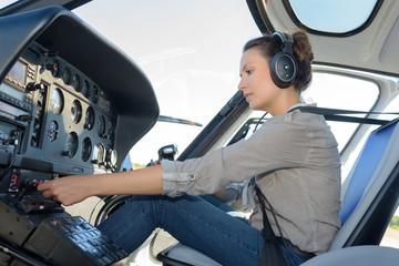 confident pilot with headset in private helicopter
