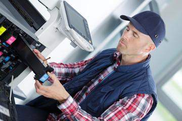 shot handsome technician fixing photocopier machine