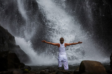 Woman practices yoga at Gitgit waterfall on Bali in indonesia
