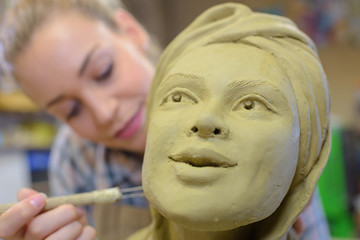 woman making ceramic face in an art class