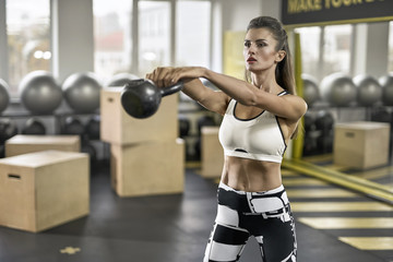 Sportive girl does exercise in gym