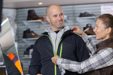 woman closing zip on sports jacket man is trying on