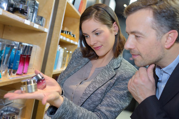 Shop assistant showing beauty products to man